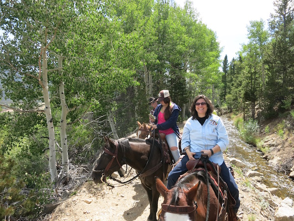 Diana enjoying a day of horseback riding at Rawah Ranch